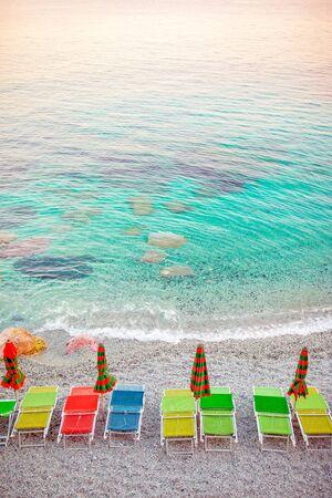 Sunbeds and umbrellas at beautiful european seashore in Monterosso, Cinque Terre, Italy