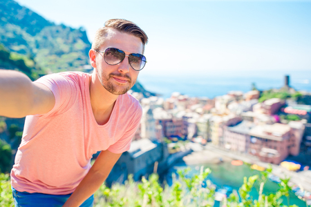 Young tourist in sunglasses taking selfie with scenic view of Vernazza, Cinque Terre, Liguria, Italy