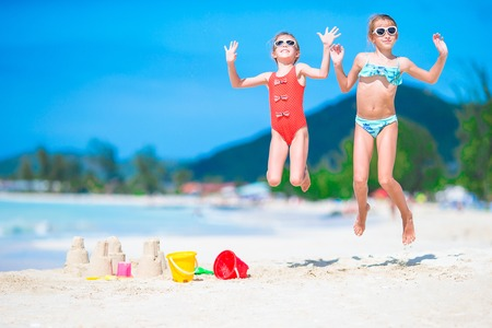 Two kids making sand castle and having fun at tropical beach Stock Photo