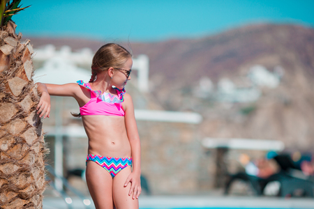 Little happy girl enjoy vacation near outdoor swimming pool Stock Photo