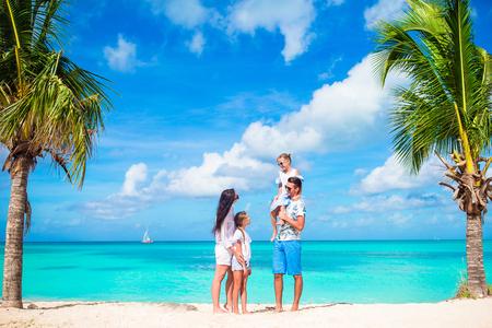 Family of four on the beach on caribbean vacation.