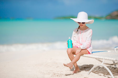 Little adorable girl with bottle of sun cream sitting at tropical beach Stock Photo