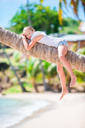 Little girl at tropical beach on palm tree during summer vacation
