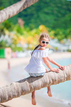 Little girl on palm tree at tropical seashore