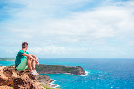Young man enjoying breathtaking views from Shirley Heights on tropical Antigua island in Caribbean