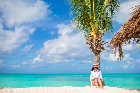 Young woman reading book during tropical white beach Banco de Imagens
