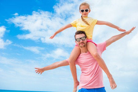 Family fun on white sand. Smiling father and adorable child playing at sandy beach on a sunny day