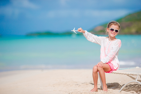 Happy little girl with toy airplane in hands on white sandy beach. Kid play with toy on the beach Stock Photo