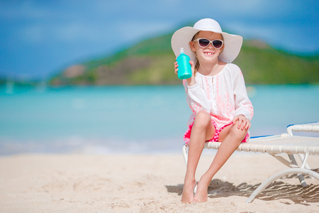 Beautiful kid with bottle of sun cream on tropical beach Banque d'images