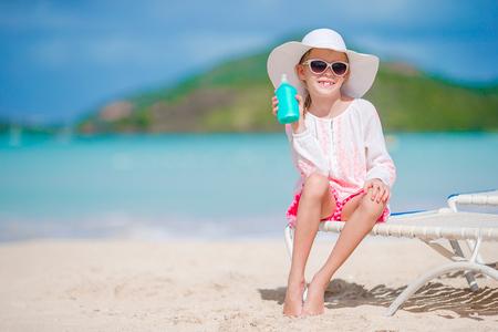 Beautiful kid with bottle of sun cream on tropical beach Standard-Bild