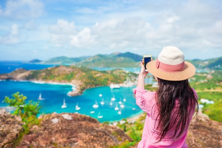 Young tourist woman making photo of English Harbor from Shirley Heights, Antigua, paradise bay at tropical island in the Caribbean Sea