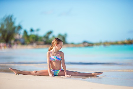 Adorable little girl sitting on white snow sand Banque d'images - 96975057