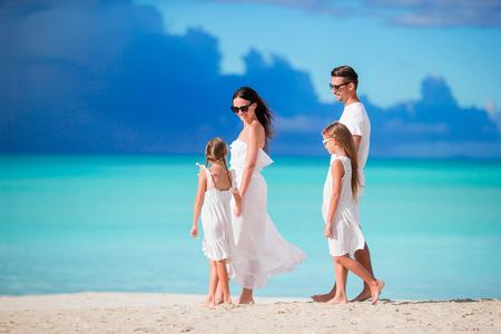 Family of four walking on white beach