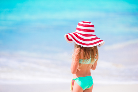 Adorable little girl in big red hat walking along white sand Caribbean beach