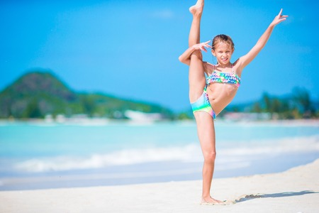 Beautiful little girl on beach having fun. Happy girl enjoy summer vacation background the blue sky and turquoise water in the sea on caribbean island 스톡 콘텐츠
