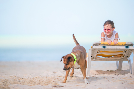 Adorable little girl on the beach playing with dog Foto de archivo