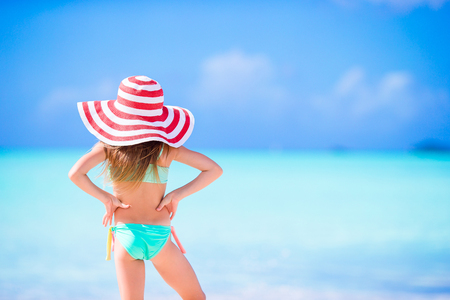 Adorable little girl in big hat walking along white sand Caribbean beach Banque d'images