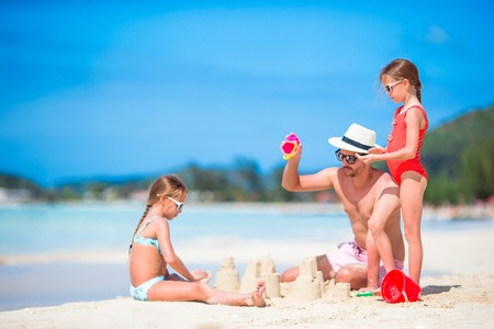 Family making sand castle at tropical white beach. Father and two girls playing with sand on tropical beach