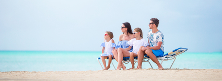 Panorama of family on the beach relaxing on the chaise-lounge