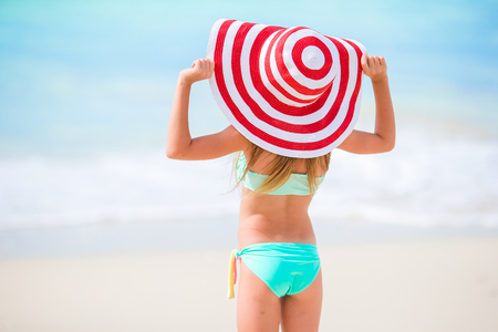 Back view of adorable little girl in big hat on white beach Stock Photo