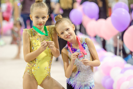 Little charming gymnasts with medals after the rhythmic gymnastics competition