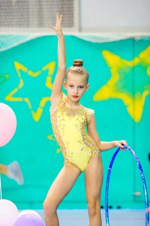 Little gymnast participates in competitions in rhythmic gymnastics Foto de archivo