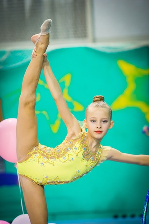 Little gymnast participates in competitions in rhythmic gymnastics Stock Photo