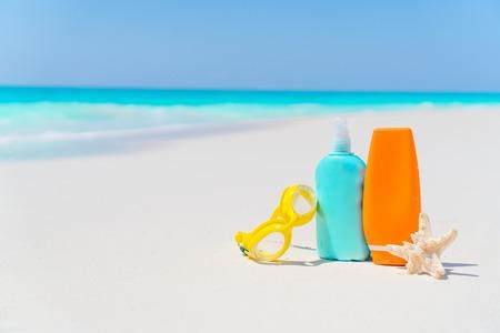 Suncream bottles, glasses, starfish on white sand beach Stock Photo