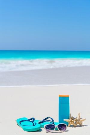 Suncream bottles, sunglasses, flip flop starfish on white sand background ocean Stock Photo