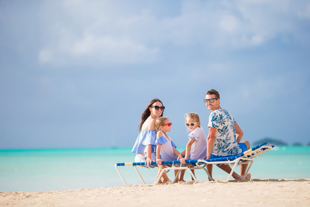 Happy beautiful family on the beach. Back view of parents and kids on the chaise-lounge