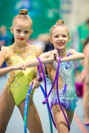 Little adorable gymnasts with medals in rhythmic gymnastics competition