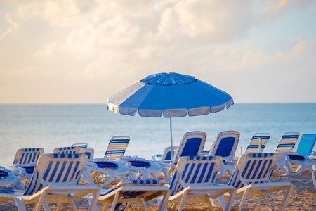 Public beach in a popular resort in the Caribbean with umbrellas and chaise-lounges