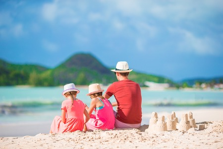 Father and little kid making sandcastle at tropical beach