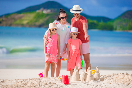 Family of four making sand castle at tropical white beach Foto de archivo