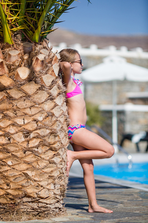 Little happy girl enjoy vacation near swimming pool