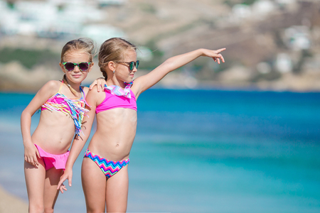 Two little girls together on the beach on vacation