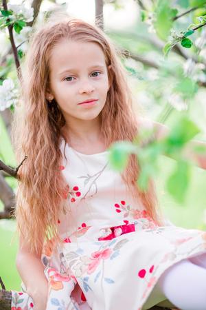 Entzückendes kleines Mädchen im blühenden Apfelbaumgarten am Frühlingstag