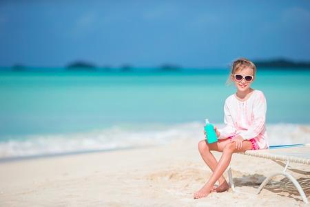 Beautiful kid with bottle of sun cream on tropical beach Stock Photo