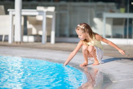 Little girl having fun with a splash near swimming pool Standard-Bild