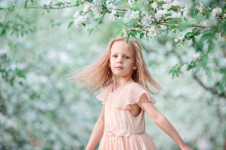 Entzückendes kleines Mädchen im blühenden Kirschbaumgarten am Frühlingstag
