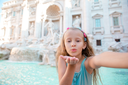 Adorable little girl taking selfie by the Fountain of Trevi in Rome.