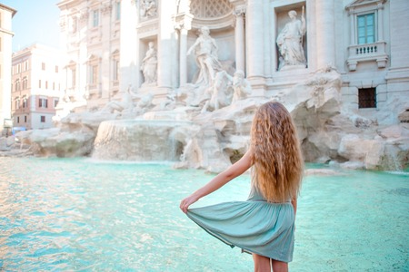 Adorable little girl background Trevi Fountain, Rome, Italy. Happy toddler kid enjoy Italian vacation holiday in Europe.