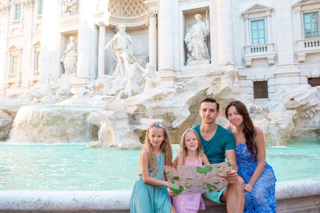 Happy family near Fontana di Trevi with city map