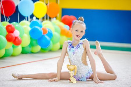 Una hermosa pequeña gimnasta mostrando la medalla y la copa ganada después de una competencia.