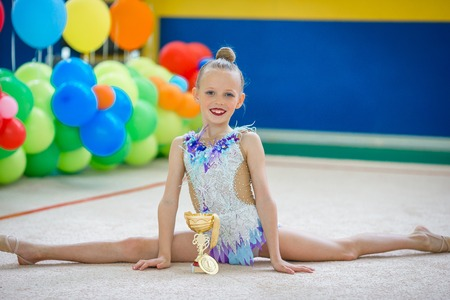 A beautiful little gymnast showing the medal and the cup won after a competition