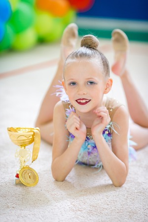 Beautiful little gymnast training on the carpet and ready for competitions