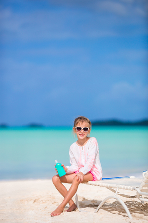 Little girl with bottle of sun cream sitting at tropical beach Stock Photo