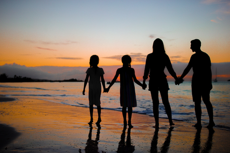 Family silhouette in the sunset at the beach
