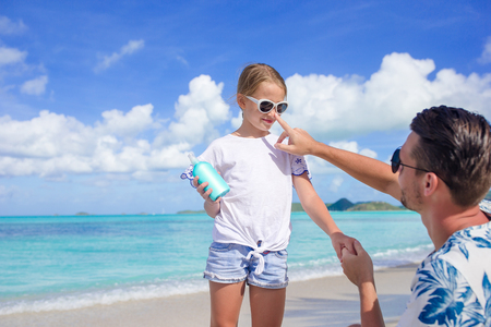 Young father applying sun cream to daughter Stock fotó