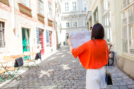 Young woman with a city map in city. Travel tourist girl with map in Vienna outdoors during holidays in Europe. 免版税图像